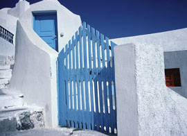 whitewashed villa with blue gate - santorini, greece